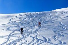 Gruppo di persone che fanno un'escursione sulle racchette da neve e sul panorama della neve della montagna con cielo blu nelle al Fotografie Stock