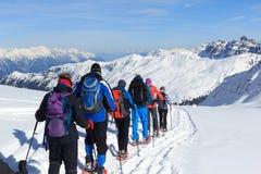 Gruppo di persone che fanno un'escursione sulle racchette da neve e sul panorama della neve della montagna con cielo blu nelle al Immagine Stock