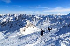 Gruppo di persone che fanno un'escursione sulle racchette da neve e sul panorama della neve della montagna con cielo blu nelle al Immagine Stock Libera da Diritti