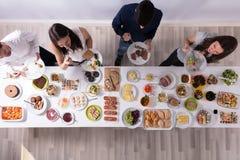 Gruppo di persone che mangiano alimento sul piatto immagine stock