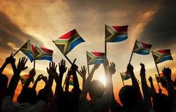Gruppo di persone che ondeggiano le bandiere sudafricane in Lit posteriore immagine stock libera da diritti