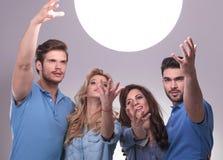 Gruppo di persone che raggiungono fuori per la grande palla di luce Immagine Stock