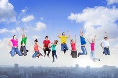 Gruppo di persone che saltano sopra la città Immagini Stock Libere da Diritti