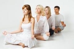 Gruppo di persone che si rilassano e che fanno yoga nel bianco Fotografia Stock