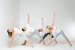 Gruppo di persone che si rilassano e che fanno yoga nel bianco Immagine Stock