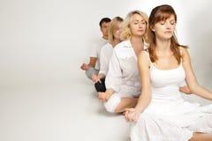 Gruppo di persone che si rilassano e che fanno yoga nel bianco Immagini Stock