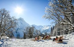 Gruppo di persone che si siedono con gli sdrai in montagne di inverno Prendendo il sole nella neve La Germania, Baviera, Allgau Fotografie Stock Libere da Diritti