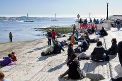 Gruppo di persone che si siedono su una scala all'aperto Fotografia Stock