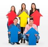 Gruppo di persone che tengono le frecce che indica su Fotografia Stock