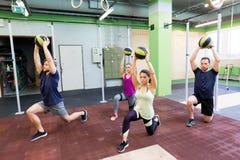 Gruppo di persone con addestramento della palla medica nella palestra Immagini Stock