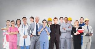 Gruppo di persone con differenti professioni che stanno davanti al fondo grigio in bianco Fotografia Stock