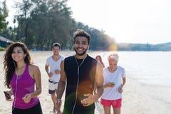 Gruppo di persone correre, corridori giovani di sport che pareggiano sulla spiaggia risolventi sorridere pareggiatori maschii e f Immagini Stock