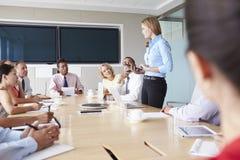 Gruppo di persone di affari che si incontrano intorno alla Tabella della sala del consiglio Immagine Stock Libera da Diritti