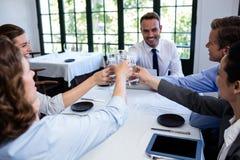 Gruppo di persone di affari che tostano bicchiere d'acqua in ristorante immagine stock