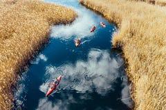 Gruppo di persone in kajak fra le canne sul fiume di autunno immagini stock