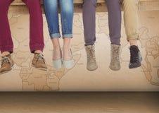 Gruppo di persone le gambe del ` s che si siedono sulla plancia di legno davanti alla mappa di mondo Fotografie Stock Libere da Diritti