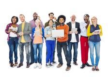 Gruppo di persone multietnico che tengono gli apparecchi elettronici Immagini Stock Libere da Diritti