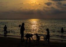 Gruppo di persone profilato sulla spiaggia e nel mare Fotografia Stock