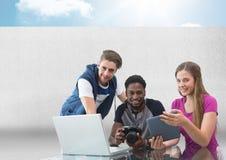 Gruppo di persone sul computer portatile con la macchina fotografica davanti a fondo grigio con il cielo Fotografie Stock Libere da Diritti