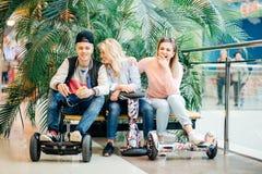 Gruppo di persone sul hoverboard elettrico del motorino che si siede al banco e che per mezzo del telefono fotografia stock libera da diritti