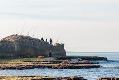 Gruppo di pescatori che pescano nella mattina sulla riva del mare Fotografia Stock