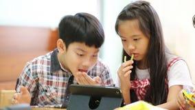 Gruppo di piccolo bambino asiatico che mangia spuntino e che gioca insieme ad una compressa del computer archivi video