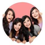 Gruppo di pigolio sorridente delle belle donne attraverso il foro del cerchio Fotografia Stock