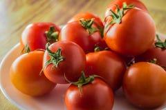 Gruppo di pomodori su un primo piano del piatto sulla tavola Immagine Stock