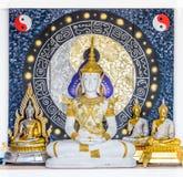 Gruppo di posizioni della statua di Buddha e di simboli di Tao sulla parete del corridoio del tempio fotografia stock
