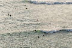gruppo di praticare il surfing nell'ambito della luce solare di sera Fotografie Stock