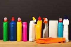 Gruppo di prodotti di pulizia variopinti su fondo scuro Fotografie Stock Libere da Diritti