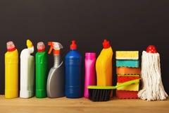 Gruppo di prodotti di pulizia variopinti su fondo scuro Fotografie Stock