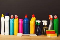 Gruppo di prodotti di pulizia variopinti su fondo scuro Immagini Stock