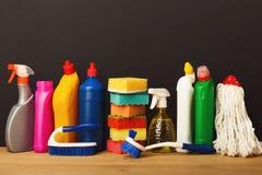 Gruppo di prodotti di pulizia variopinti su fondo scuro Fotografia Stock