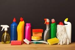 Gruppo di prodotti di pulizia variopinti su fondo scuro Fotografia Stock Libera da Diritti