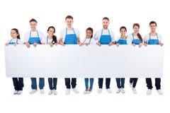 Gruppo di pulitori che tengono un'insegna bianca in bianco Fotografia Stock