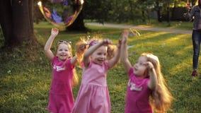 Gruppo di ragazza felice dei piccoli bambini che gioca il grande ventilatore di prova della bolla di sapone dell'aria del fermo archivi video