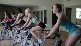 Gruppo di ragazze che per mezzo delle bici di esercizio per prepararsi stock footage