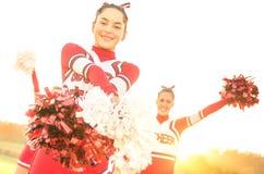 Gruppo di ragazze pon pon che eseguono al campo della High School Immagine Stock
