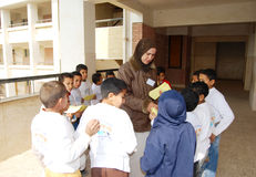 Gruppo di ragazzi in un cerchio che ottiene i distintivi dall'insegnante femminile Fotografia Stock Libera da Diritti
