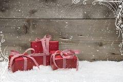 Gruppo di regali di Natale rossi, con neve su grey  Fotografie Stock