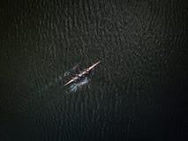 Gruppo di rematura accademico di af del colpo aereo del fuco in canoa sul fiume scuro fotografie stock