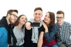 Gruppo di riusciti giovani che si siedono sul banco, a sorridente Fotografia Stock Libera da Diritti
