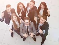 Gruppo di riusciti impiegati che mostrano i pollici su Fotografia Stock
