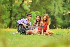 Gruppo di riusciti studenti con un riposo della chitarra Fotografia Stock
