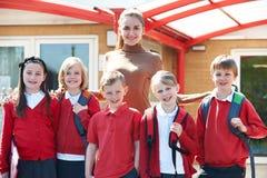 Gruppo di scolari con l'insegnante In Playground Fotografie Stock