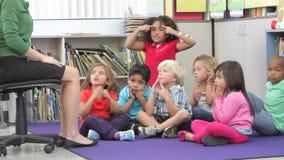 Gruppo di scolari elementari di età che imparano le parti del loro fronte archivi video