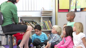 Gruppo di scolari elementari di età che imparano leggere stock footage