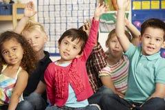 Gruppo di scolari elementari di età che rispondono alla domanda nella classe Immagini Stock