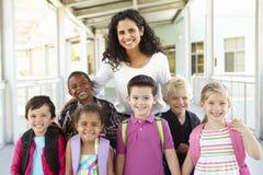 Gruppo di scolari elementari di età che stanno fuori con il tè Fotografia Stock